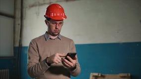 De man houdt een telefoon in zijn hand op het hoofd van een ingenieur een beschermende helm stock footage