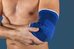 De man houdt de elleboog aan scherpe pijn gepast Geïsoleerdr op een blauwe achtergrond stock afbeeldingen