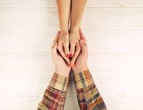 De man houdt hoogste de meningsbeeld van vrouwen` s handen op witte houten achtergrond Paar in liefdeconcept Stock Fotografie