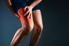 De man houdt op de knie, de pijn in de knie stock afbeeldingen