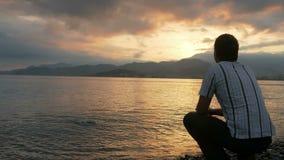 De man kijkt in een overhemd bekijkend de zonsopgang op het strand van de oceaan De zon neemt toe van achter de bergen E stock footage