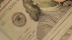 De man kijkt meer dan een pak met nota's van dollars in handen Nominale waarden van dollars Een groot aantal dollars stock footage
