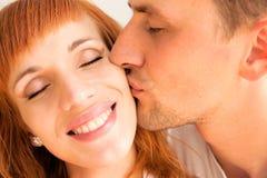 De man kust zijn vrouw op de wang stock foto's