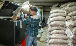 De man laadt de korrels in de vaste brandstofboiler, economisch h stock fotografie
