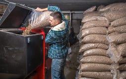 De man laadt de korrels in de vaste brandstofboiler, het economische verwarmen stock fotografie