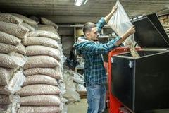 De man laadt de korrels in de vaste brandstofboiler, het economische verwarmen royalty-vrije stock fotografie
