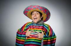 De man in levendige Mexicaanse poncho tegen grijs Royalty-vrije Stock Foto's