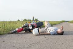 De man ligt op het asfalt dichtbij de motorfiets, het thema van verkeersongevallen royalty-vrije stock foto