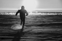 De man loopt langs het ijs van de rivier Royalty-vrije Stock Foto's