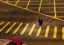 De man loopt op de gestreepte kruising stock fotografie