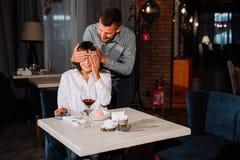 De man maakt een verrassing voor een vrouw in het restaurant royalty-vrije stock foto