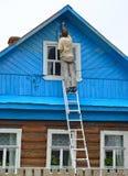De man maakt omhoog een voorgevel van het blokhuis, die zich op een ladder bevinden stock foto's