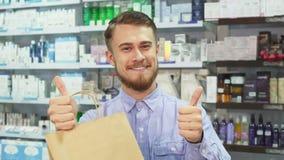 De man maakte een aankoop in een drogisterij en het tonen van duimen stock videobeelden