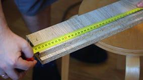 De man meet de afstand op de raad met een meetlint en merkt de teller Het huiswerk met meubilair stock footage