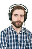 De man met een baard in oortelefoons Stock Fotografie