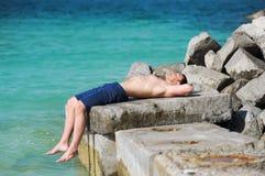 De man met een naakt torso die op een steen tegen de achtergrond van het overzees liggen stock foto's