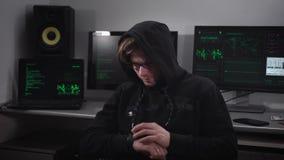 De man met glazen en een kap van katten die in een geheime plaats op het hoofd zitten en controleren de gecodeerde berichten die  stock videobeelden