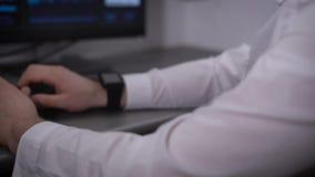 De man met glazen en een wit overhemd die zeer snel op de computer typen tikken en staren bij de monitor in stock footage