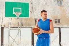 De man met het basketbal buiten op de Speelplaats Stock Afbeeldingen