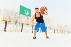 De man met het basketbal buiten op de Speelplaats Royalty-vrije Stock Foto's