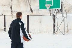 De man met het basketbal buiten op de Speelplaats Stock Foto