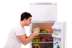 De man naast koelkasthoogtepunt van voedsel Stock Foto's