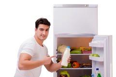 De man naast koelkasthoogtepunt van voedsel Royalty-vrije Stock Foto's