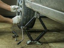 De man neemt het wiel van de bruine auto in de garage Royalty-vrije Stock Afbeelding