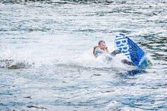 De man oefent het begin van de surfplankdia op uit wa stock afbeelding