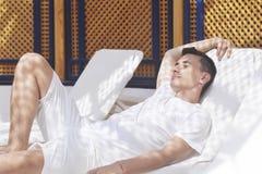 De man ontspant na een kuuroord De man na de massage Een mens rust in een massage na een bad Een mens ligt binnen op een lanterfa Stock Afbeelding