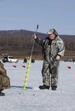 De man op de ijs visserij Stock Fotografie