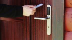 De man opent de deur voor een elektronische sleutel - kaart stock videobeelden
