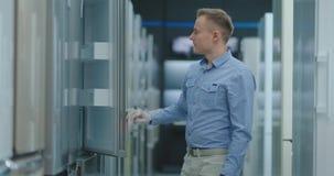 De man opent de deur van de ijskast in de toestellenopslag en is met andere modellen vergelijkbaar om het nieuwe huis te kopen stock footage
