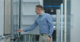 De man opent de deur van de ijskast in de toestellenopslag en is met andere modellen vergelijkbaar om het nieuwe huis te kopen stock videobeelden