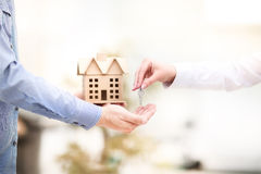 De man overhandigt een huissleutel aan een vrouw Sleutel met een keychain in de vorm van het zijn huis stock foto's