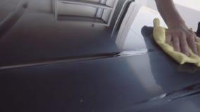 De man poetst de auto op stock video