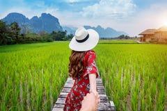 De man ` s van de vrouwenholding hand en het leiden van hem tot Houten weg en groen padieveld in Vang Vieng, Laos royalty-vrije stock afbeeldingen