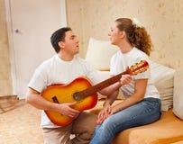 De man speelt een gitaar voor het meisje Royalty-vrije Stock Fotografie