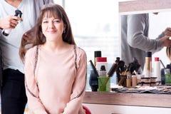 De man stilist die met vrouw in schoonheidssalon werken royalty-vrije stock afbeelding