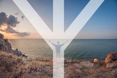De man symboliseert de rune van mannaz, zit de man op het strand, eerste-persoonsmening, de vervorming van het vissenoog royalty-vrije stock afbeelding