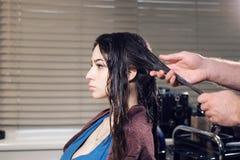 De man van de close-upkapper maakt kapsel voor jonge vrouw in schoonheidssalon royalty-vrije stock afbeeldingen