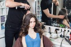 De man van de close-upkapper maakt kapsel voor jonge vrouw in schoonheidssalon stock fotografie