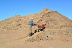 De man van gemiddelde jaren is gelukkig een kruiwagen met grond op roa Royalty-vrije Stock Foto