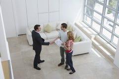 De Man van makelaar in onroerend goedshaking hands with door Vrouw in Nieuw Huis Stock Fotografie