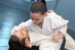 De man van de vrouwenholding in karategreep op vloer stock fotografie