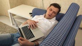 De man viel in slaap terwijl het werken in laptop aan zijn bank in zijn stadsflat stock footage