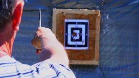 De man werpt een mes in het doel van een afstand, de messenklappen het doel Het werpen van messen bij het doel van stock video