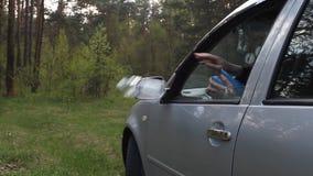 De man werpt het huisvuil in openlucht uit de auto stock video