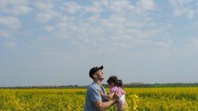 De man werpt het kind De man werpt omhoog het kind De papa en de dochter spelen in aard Gelukkige familie op een gele weide stock footage