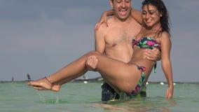 De man werpt Vrouw in Water en het Bespatten stock footage